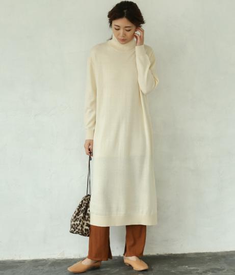 タートルネックの白ニットワンピースを着た女性